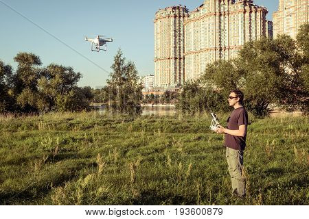 Man operating a drone quad copter with onboard digital camera in the city park