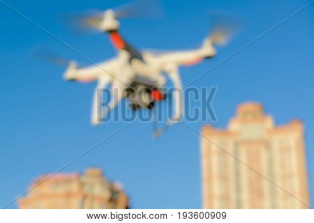 Abstract blur drone quad copter with onboard camera flying over the city in the blue sky for background