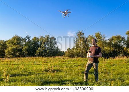 Man operating a drone quad copter with onboard digital camera in a park