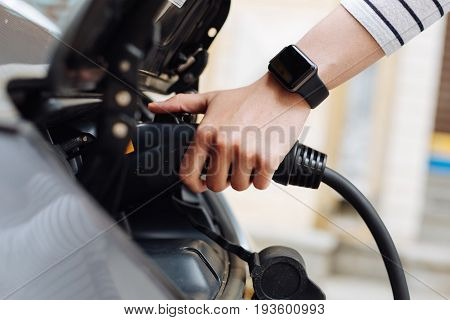 Nature-friendly. The side view of a delicate female hand plugging in a charger into the battery system of an electric car at the charging station