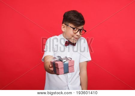 Boy in glasses outstretching small giftbox and looking at camera on red background.