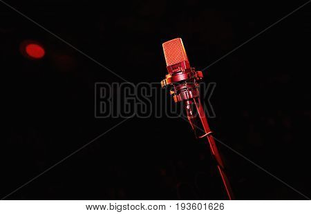 Red Microphone on dark background. Retro microphone. A microphone on stage. A pub. Bar. Restaurant. Classic. Evening. Night show. European restaurant. European bar. American restaurant. American bar.