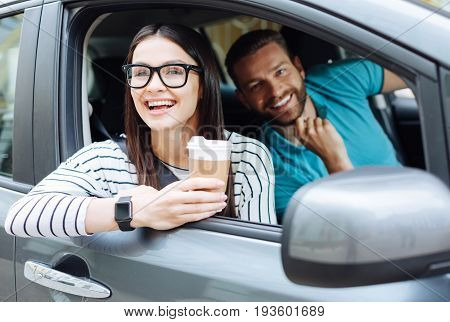Quality time together. Beautiful bearded man looking at the camera with a broad smile while his charming girlfriend sitting next to him, looking out of car window and admiring the view