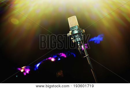 Microphone with golden rays of light. Retro microphone. A microphone on stage. A pub. Restaurant. Classic. Evening. Night show. European restaurant. European bar. American restaurant. American bar