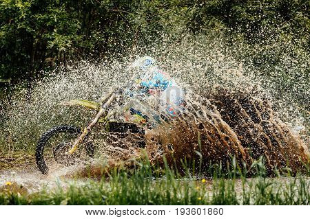 motorcycle rider crosses puddle splashes of water and dirt