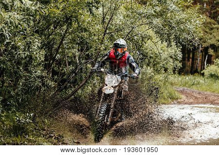 enduro athlete on motorcycle crosses a puddle of water and mud racing motocross
