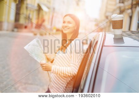 Sunny day. Pleasant beautiful woman enjoying sunny day in the city while examining the map and planning the next travel itinerary while the focus of the photo being on the coffee cup on car top