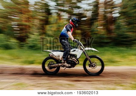 blurred motion motorcyclist enduro racing motocross in woods