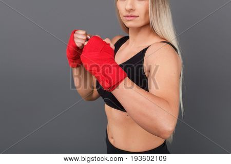 Blonde woman holding hands wrapped in red bandages in boxing pose.