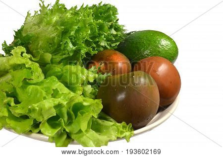 Fresh washed vegetables to prepare a green salad on large ceramic dish: ripe avocado, three black tomatoes