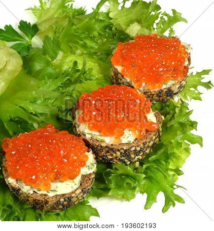 Three small sandwiches of black baguette with grains of cereals and poppy seeds, with red caviar and butter, knocked down with finely chopped dill, lie on green leaves of crispy leaf lettuce. Isolated on white background