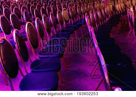 Colored chairs in the cave before the concert. Chairs in the concert hall. Empty rows of red seats in cave.