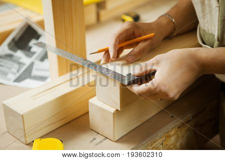 Craftsman measure wooden planks with help of ruler. Woodworker at workshop projecting details of processed material. Carpenter does measurements according to project