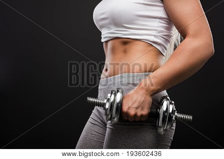Crop anonymous woman in sportswear holding heavy metal dumbbell on black background.