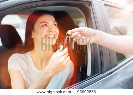 There you go. Gorgeous young woman sitting in the driver seat of a car and receiving her car keys from a strong male hand