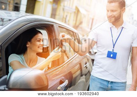 Amazing service. Handsome car rental agency employee handing car keys to a happy beautiful woman sitting in the driver seat and accepting them willingly