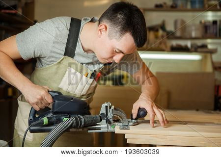 Man working with carving equipment in workshop. Electronic device makes chinseling groove in wooden bar, worker carpenter in apron at workplace