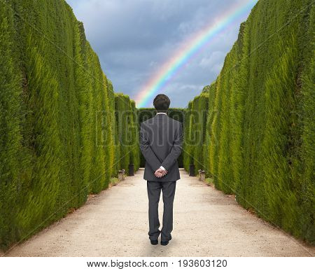 Young businessman watching the rainbow in the park