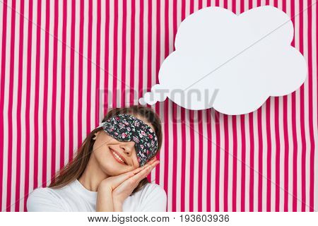 Young lovely girl in sleeping mask posing as sleepy with white speech bubble on striped background.