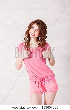 girl pinup-style in a pink dress shows symbols with their hands