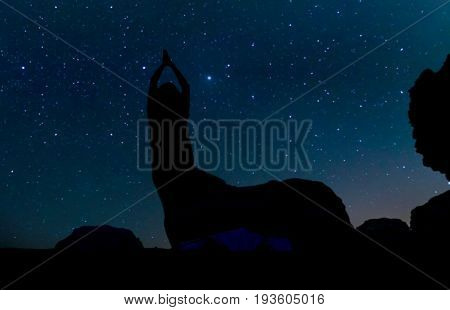 Silhouette of young woman doing yoga practice on the sand hill beneath the stars Milky Way and a lot of stars over the mountain at Wadi Rum desert. Concept for happiness traveling and freedom.