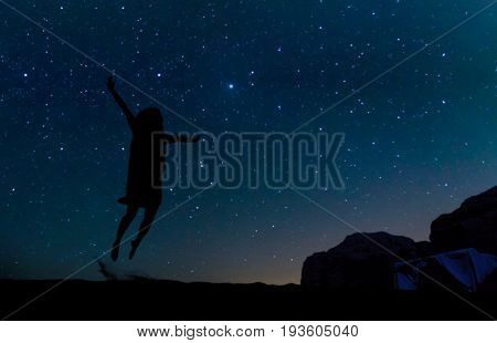 Silhouette of young woman jumping over sand hill beneath the stars Milky Way and a lot of stars over the mountain at Wadi Rum desert. Concept for happiness traveling and freedom.