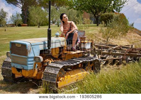 Beautiful woman driving vintage tractor