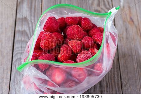 Frozen strawberries in a plastic bag on a wooden background