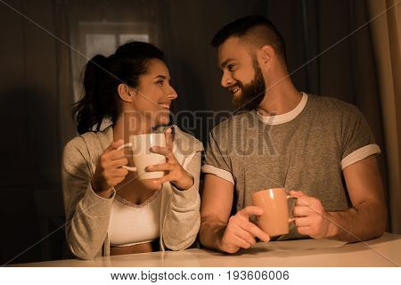 Young Sweethearts Smiling While Sitting At Table And Drinking Coffee At Home