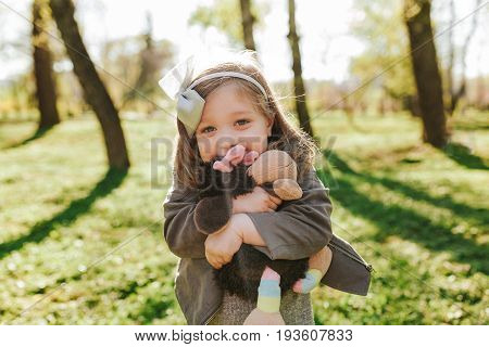 Portrait of cheerful girl embracing plush toy and smiling at camera in park.