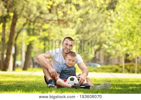 Father and son with soccer ball sitting on green grass in park
