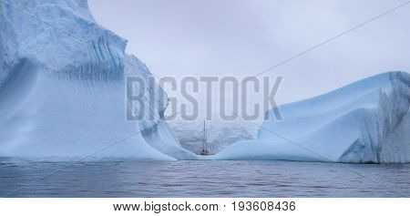 The ship swims between the huge icebergs. Huge icebergs are washed by the sea. Wide-angle frame of icebergs and a small vessel. The sky is covered with clouds and fog.
