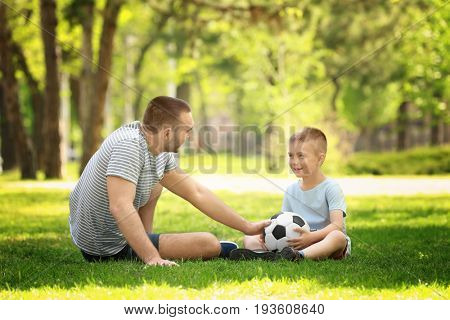 Father and son playing with soccer ball on green grass in park