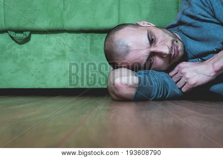 Loneliness. Sadness. Depression. Lonely and depressed man lying on the floor of his home. He is missing someone.