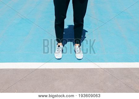 Cropped Image Of Female Legs In Sneakers And Black Pants Are On A Blue Sports Field In Front Of The