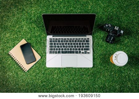 Top View Of Laptop, Smartphone, Photo Camera And Coffee To Go On Green Grass