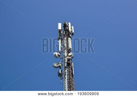 Communication tower antenna with blue sky background .