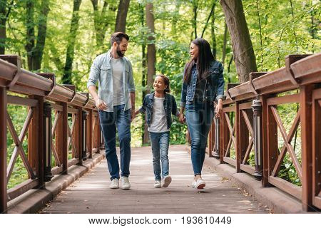 Young Smiling Interracial Family Holding Hands And Walking Through The Wooden Bridge In Forest