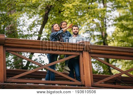Young Happy Interracial Family Standing On Wooden Bridge, While Mother Pointing Somewhere