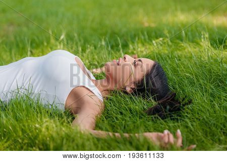 side view of smiling woman lying on green grass with outstretched arms