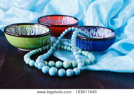 turquoise earrings on bowl. Fashion background on silk