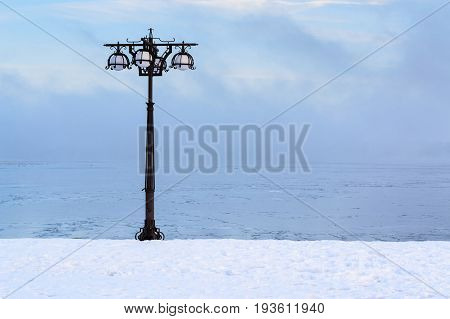 Snowy Embankment Along The Misty River With Lantern At The Foggy Morning - Winter Landscape.