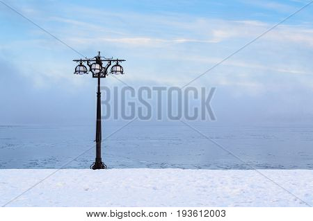 Snowy Embankment Along The Misty River With Lantern At The Foggy Morning - Winter Landscape. I