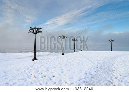 Snowy Embankment Along The Misty River With Lanterns At The Foggy Morning - Winter Landscape. I