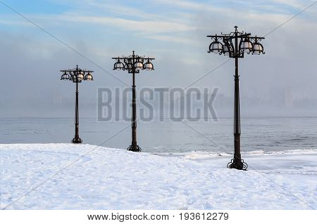 Snowy Embankment Along The Misty River With Lanterns At The Foggy Morning - Winter Landscape. Ii