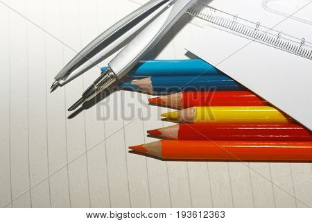 This is photo of crayons with ruler and compass on exercise book and a paper.