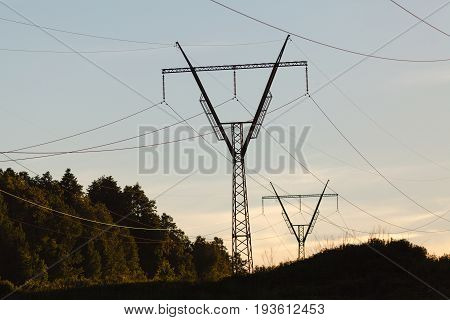 Electricity Pylons, Power Lines And Trees Silhouetted Against A Cloudy Sky At Sunset