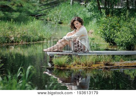 Portrait of a beautiful girl in Slavic clothes. Young barefoot woman is sitting by the pond. Summertime