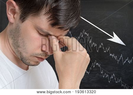 Young Unhappy And Disappointed Man And Chart With Arrow Down On