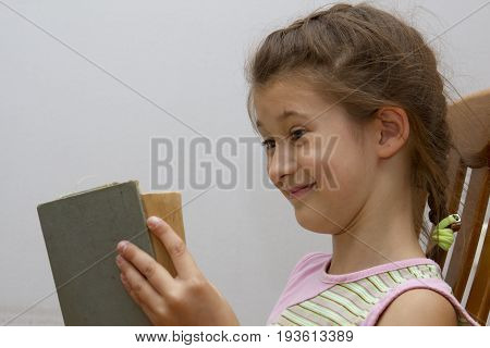 Cute little brunette relaxing and enjoying a good storybook at home fun